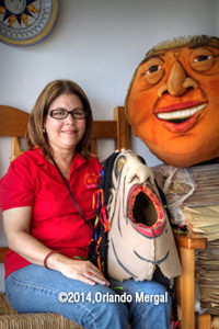 "Carmen Julia Díaz with her favorite ""cabezudo"" masks: ""Maximina La Loca"" and ""La Billetera""."
